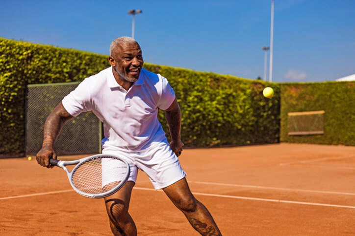 middle aged black man playing tennis - best hip and knee replacement surgeons in portsmouth nh