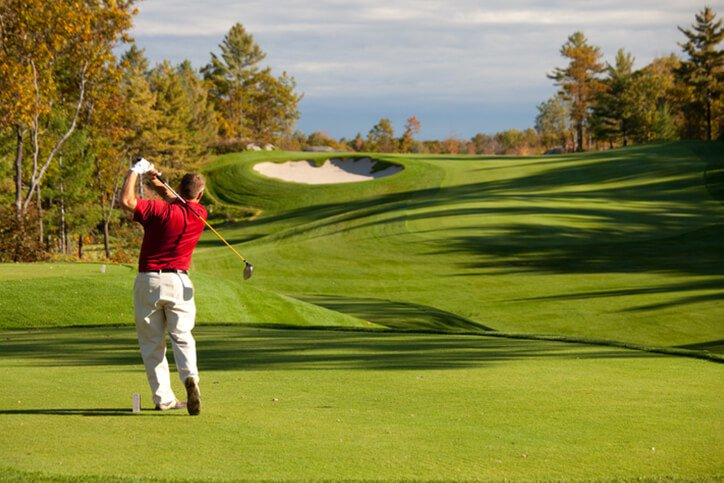man hitting off tee at golf course  - best knee replacement surgeons in Portsmouth, New Hampshire