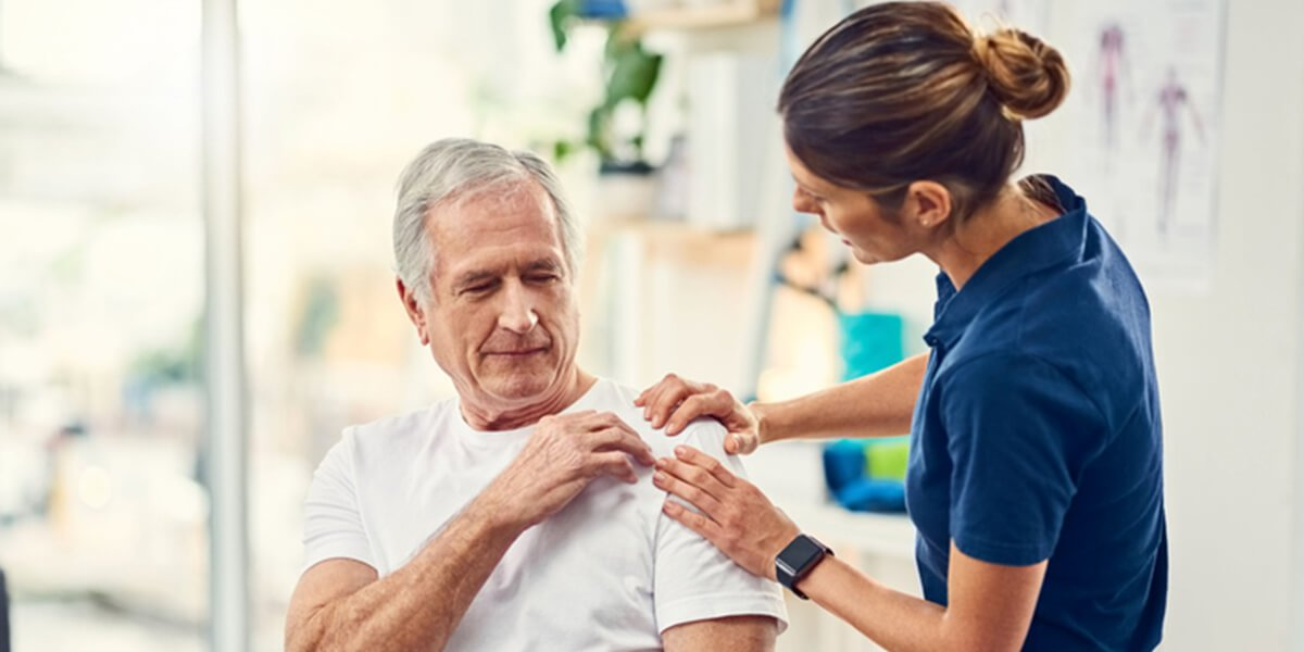 nurse examines shoulder middle aged man - best shoulder replacement surgeons in portsmouth nh
